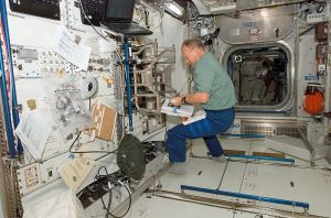 Astronaut Hans Schlegel using handrails with his feet to keep him in place
